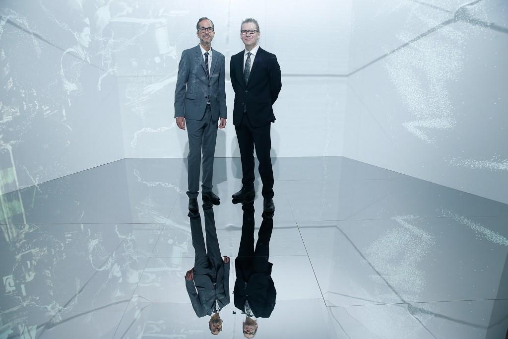Herve Mikaeloff y el artista Charles Sandison posan en la instalación de arte de este
